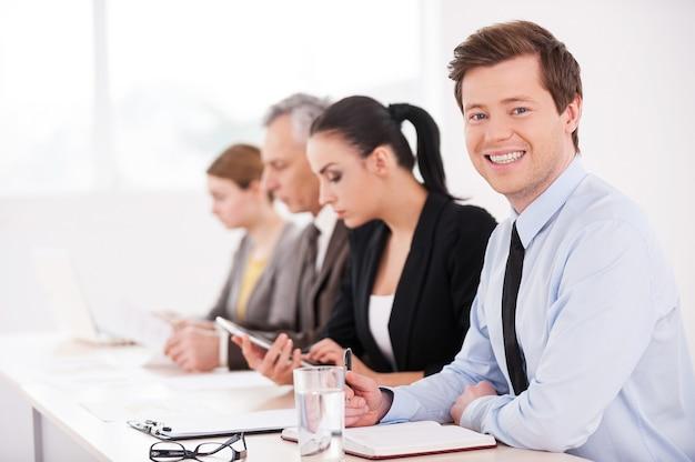 Бизнес-семинар. вид сбоку уверенных деловых людей, сидящих в ряд за столом, в то время как один мужчина смотрит в камеру и улыбается