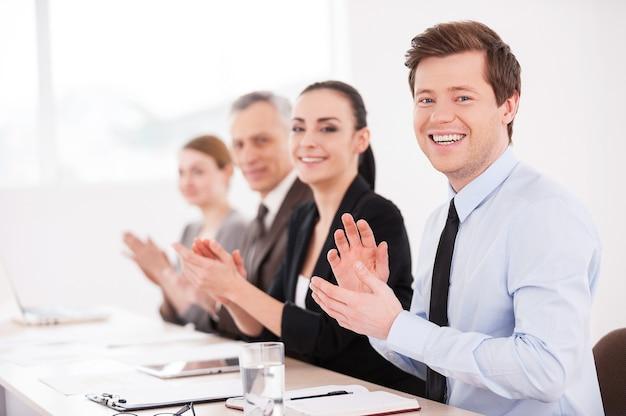 Бизнес-семинар. вид сбоку улыбающихся деловых людей, сидящих в ряд за столом и аплодирующих вам