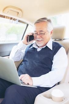 Деловой старший богатый человек, игрок биржевого трейдера в костюме, работающий с портативным компьютером и использующий смартфон в своей машине, концепция для успеха в старшем бизнесе