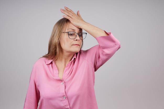 안경 사업 고위 여자는 두통이있다. 복사 공간이 회색 배경에 스튜디오 사진.