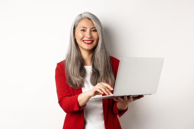 Бизнес. старший женщина, работающая на ноутбуке, носить офисное оборудование и улыбается, стоя на белом фоне.