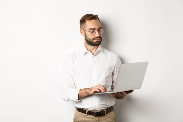 Бизнес. серьезный менеджер, работающий на ноутбуке, стоя