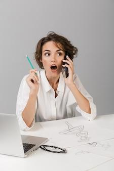 Деловая женщина в шоке, позирующая изолированно над серой стеной, сидит за столом и разговаривает по телефону