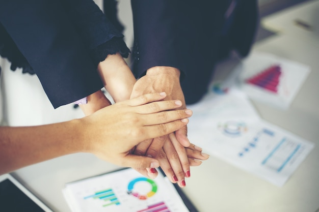 Business showing team work and giving five after signing agreement or contract