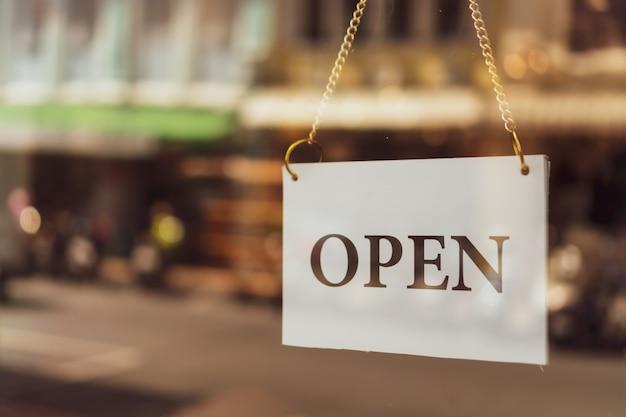 """카페 또는 레스토랑에서""""열기""""라고 표시된 비즈니스 표지판이 입구에 걸려 있습니다. 빈티지 색조 스타일."""