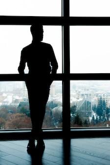 비즈니스 실루엣입니다. 창 앞에 서 있는 사업가의 전체 길이 실루엣