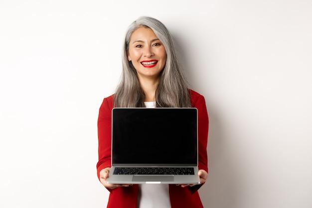 Бизнес. улыбающаяся азиатская бизнес-леди показывает пустой экран цифрового планшета, стоя на белом фоне