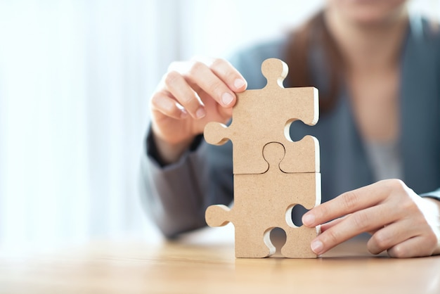 Business solutions partnership and strategy concept, businesswoman hand connecting jigsaw puzzle on desk.