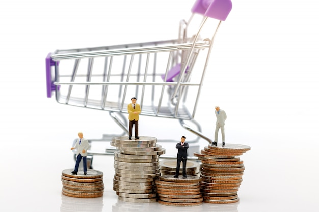 Business standing on stack of coins with shopping cart.