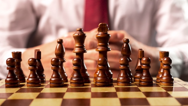 Business start up and control concept. male hands and chess board under control of boss.
