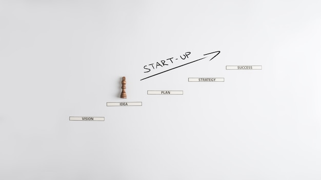 Business start up - king chess figure climbing up the paper cut steps towards success in new business