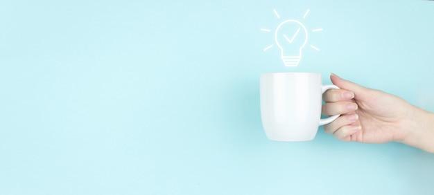 사업 시작 또는 성공 목표. 여자 손은 파란색 배경에 전구 기호 아이콘이 있는 모닝 커피 컵을 잡고 있습니다. 솔루션 분석 및 개발, 혁신적인 기술.