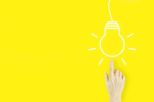 사업 시작 또는 성공 목표. 혁신, 브레인스토밍, 영감 및 솔루션 개념. 노란색에 전구 홀로그램으로 가리키는 젊은 여자의 손 손가락. 솔루션 분석이 개발됩니다.