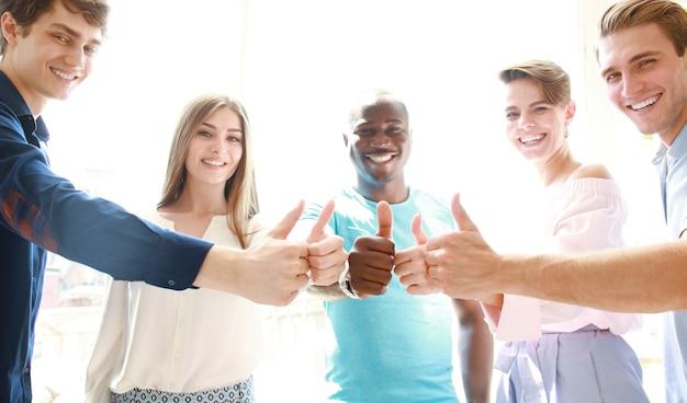 Бизнес, запуск и концепция офиса - счастливая творческая группа показывает палец вверх в офисе.