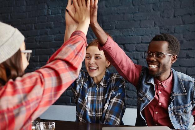 ビジネス、スタートアップ、チームワーク。カフェでの成功を祝う、カジュアルな服装で起業家の幸せで熱狂的なクリエイティブチームがお互いにハイタッチをしている
