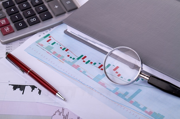 Business statistics concept with statistic graphs with glass magnifier