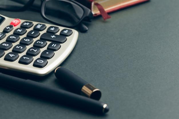 Бизнес натюрморт с калькулятором на столе в офисе.