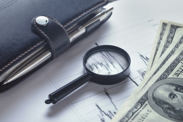 Business still-life with a magnifying glass, diary and bills