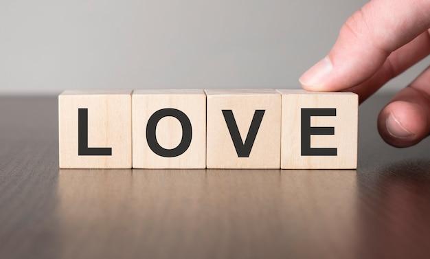 Концепция бизнес-стратегии. рука и любовь на деревянном кубическом блоке.