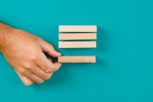 청록색 테이블에 사업 전략 개념 평면 배치. 손으로 당기거나 나무 블록을 배치.