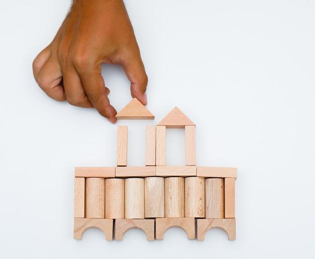 Концепция бизнес-стратегии на белом фоне плоской планировки. человек строит замок из деревянных блоков.