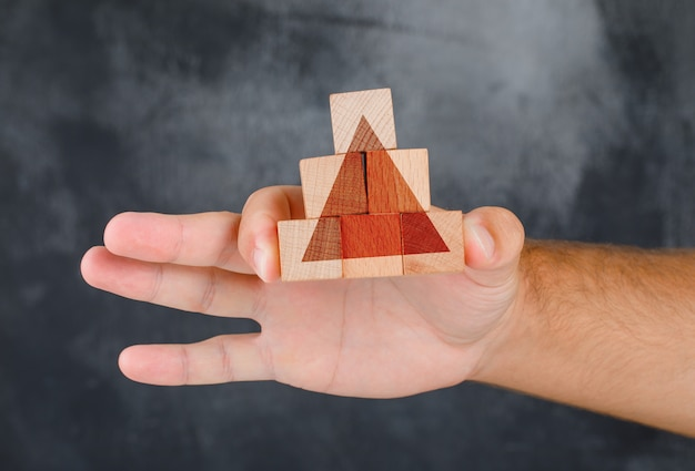 Business strategy concept side view. hand holding pyramid of wooden block.