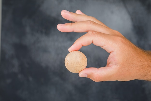 Business strategy concept side view. hand holding wooden sphere.