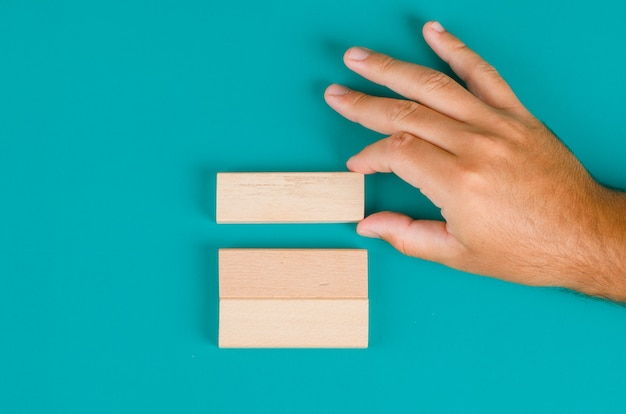 Business strategy concept on turquoise table flat lay. hand pulling or placing wooden block.