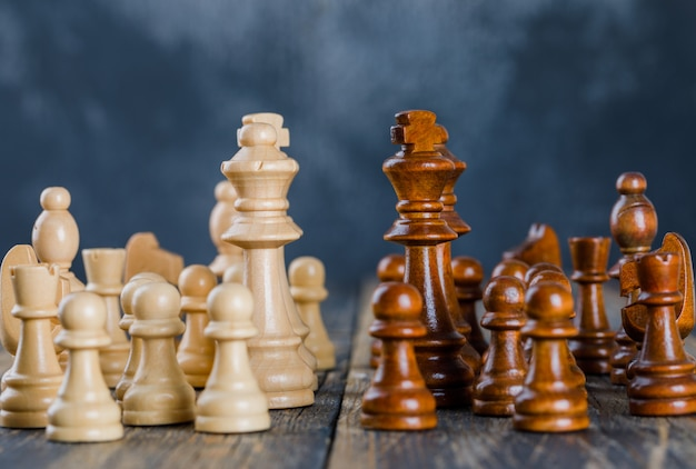 Business strategy concept with chess figures on dark and wooden surface