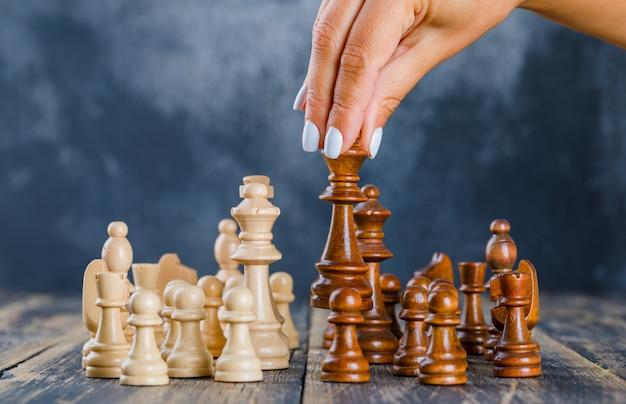 Концепция бизнес-стратегии с шахматными фигурами на темной и деревянной поверхности