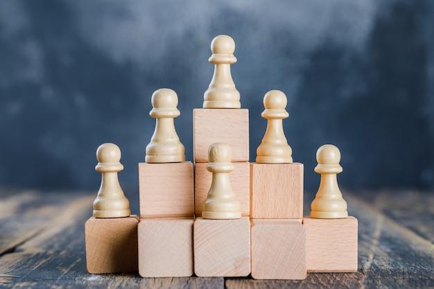 Концепция бизнес-стратегии с шахматными фигурами на игрушечных деревянных лестницах