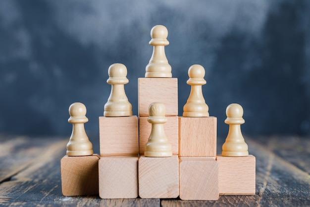 Business strategy concept with chess figures on toy wooden ladders