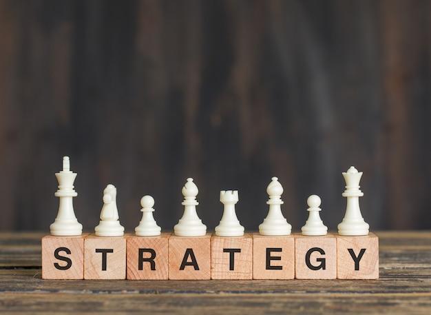 Концепция стратегии бизнеса с шахматными фигурами на деревянных кубиках на взгляде со стороны деревянного стола.