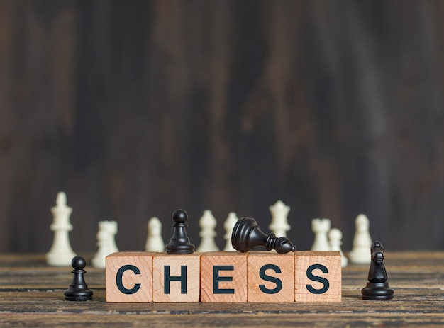 Business strategy concept with chess pieces, wooden cubes on wooden table side view.