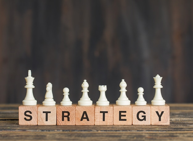 Business strategy concept with chess pieces on wooden cubes on wooden table side view.