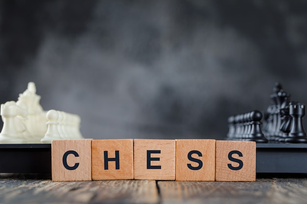Business strategy concept with chessboard and figures, wooden cubes on foggy and wooden table side view.