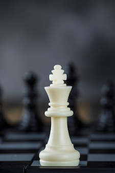 Business strategy concept with figures on chessboard on blurred and wooden table close-up.