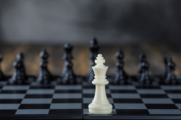 Business strategy concept with figures on chessboard on blurred and wooden table side view.