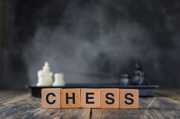 Business strategy concept with figures on chessboard, wooden cubes on foggy and wooden table side view.