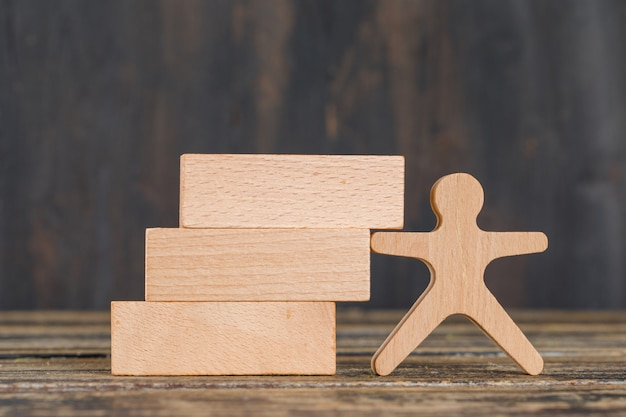 Business strategy concept with wooden blocks, human figure on wooden table side view.