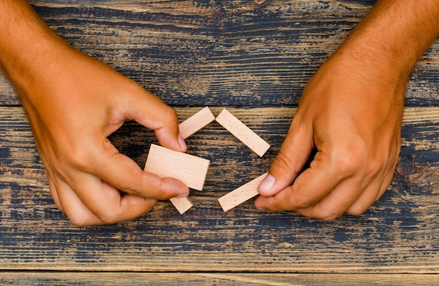 Business strategy concept on wooden background flat lay. hand holding wooden blocks.