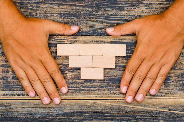 Business strategy concept on wooden background flat lay. hands protecting wooden blocks.