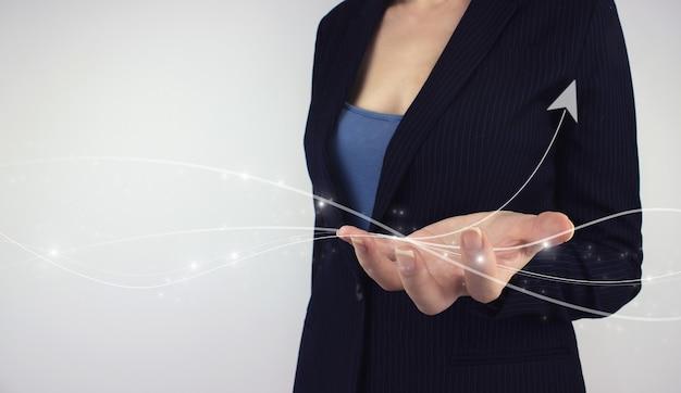 사업 전략. 디지털 마케팅 개념입니다. 회색 배경에 긍정적인 성장 아이콘의 디지털 홀로그램 화살표를 손으로 잡으십시오. 주식 시장 또는 외환 거래 금융 투자 개념.
