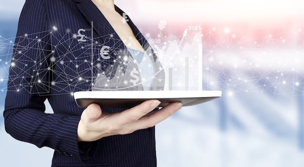 Business strategy. digital marketing. hand hold white tablet with digital hologram growth graph chart sign on light blurred background. plan growth and increase of positive indicators in business.