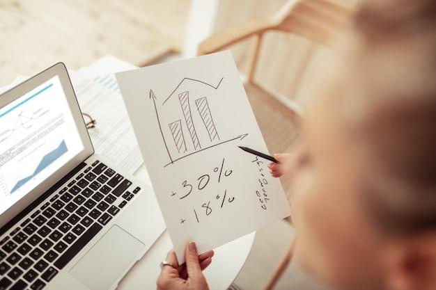事業戦略。彼女の手書きと彼女のラップトップを使用して図を扱う賢いビジネスウーマン。