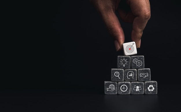 Business strategy with growth success process for leadership and teamwork concept. hand putting business target icon on dice cube blocks stack pyramid shape on dark background with copy space.
