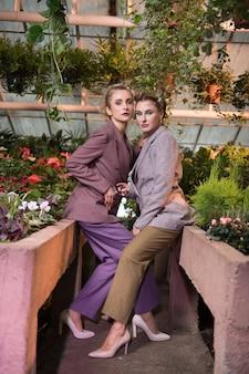비즈니스 스타일. 온실에서 사진 촬영을하면서 세련된 의상을 입고 자신감 넘치는 여성