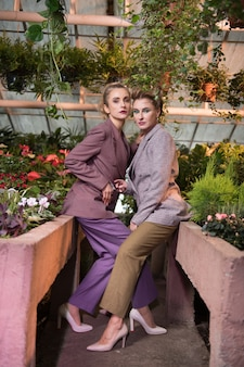 Business style. nice confident women wearing stylish costumes while having a photo shoot in the greenhouse