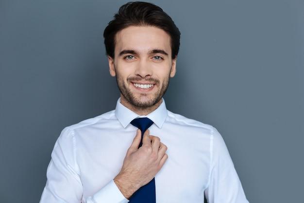 ビジネススタイル。彼のネクタイを修正しながら笑顔であなたを見ている素敵なうれしそうなハンサムなビジネスマン