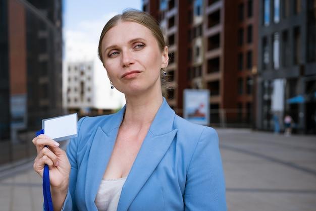 파란색 재킷에 비즈니스 세련된 여자는 그녀의 손에 id 카드를 보유